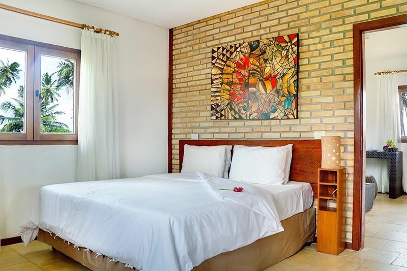 Bangalô vista para piscina com detalhes da cama casal