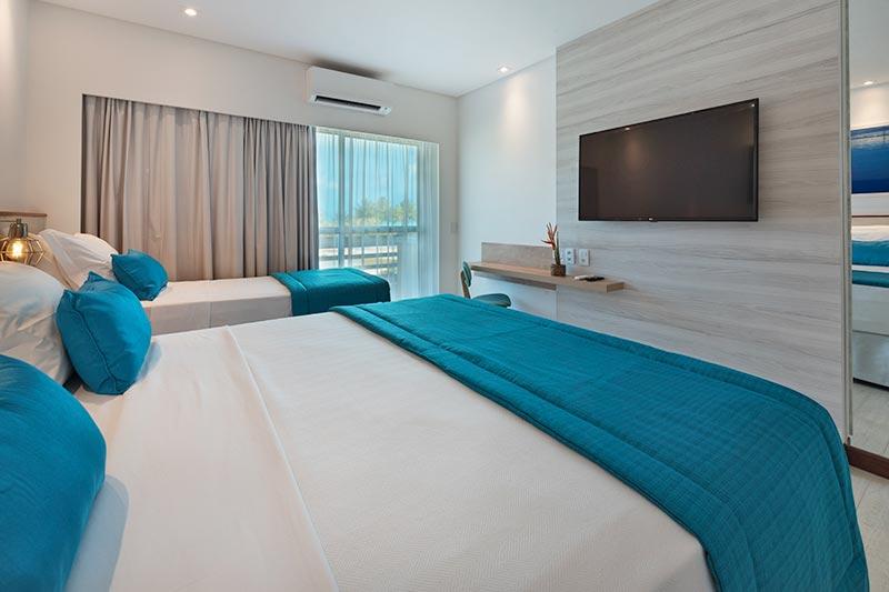 Detalhes em azul da colcha cama casal com varanda ao fundo