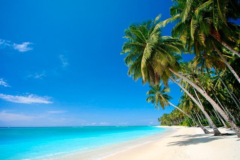 Praia com areia clara e aguas tranquilas