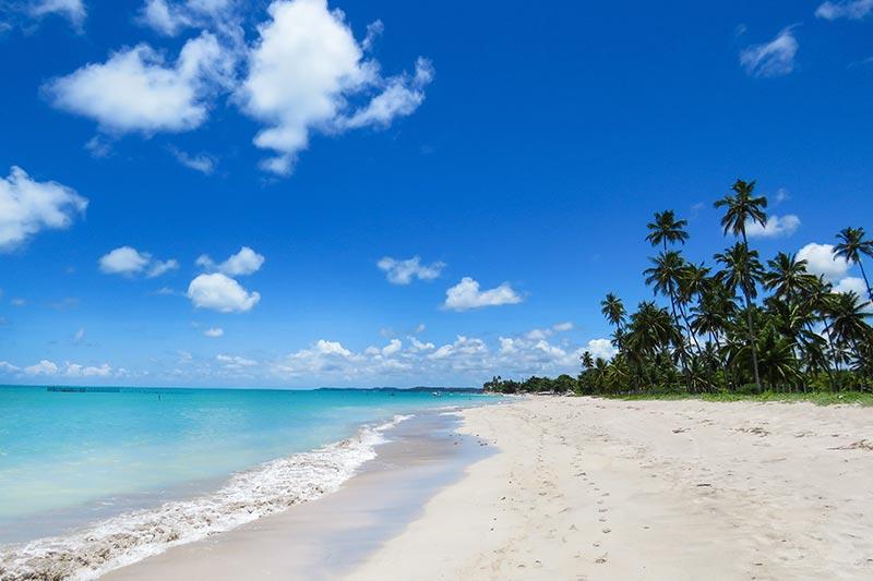 Praia com areia limpa e mar calmo ideal para família