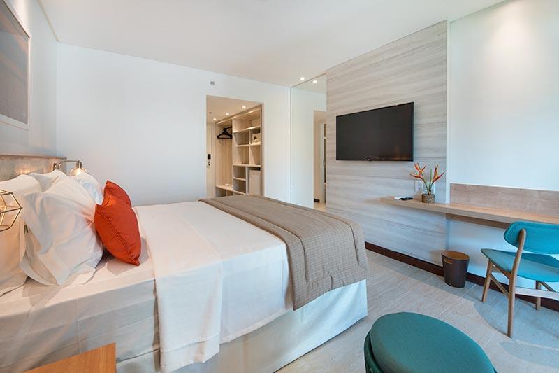 Acomodação Smart com detalhes cama casal travesseiros laranja